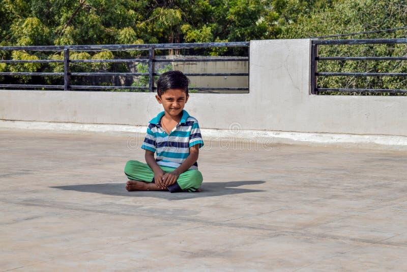 Unge som sitter under det ljusa solljuset som poserar för en bild fotografering för bildbyråer