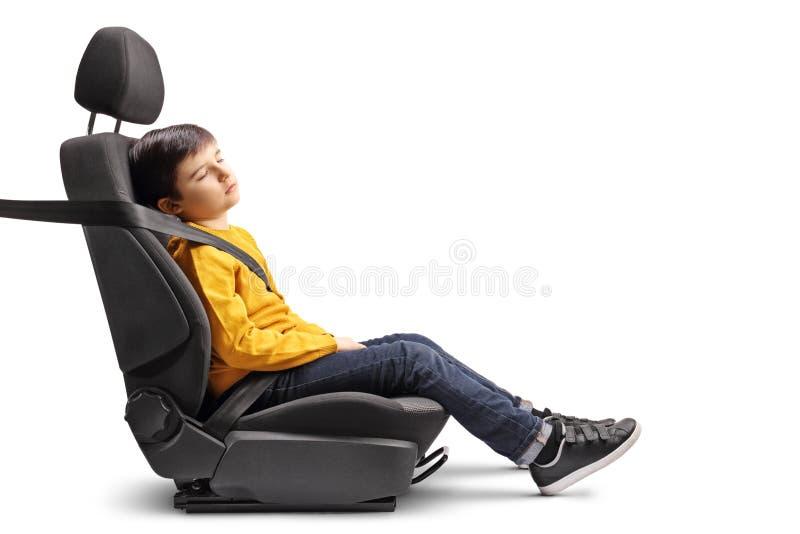 Unge som sover i ett bilsäte arkivbild
