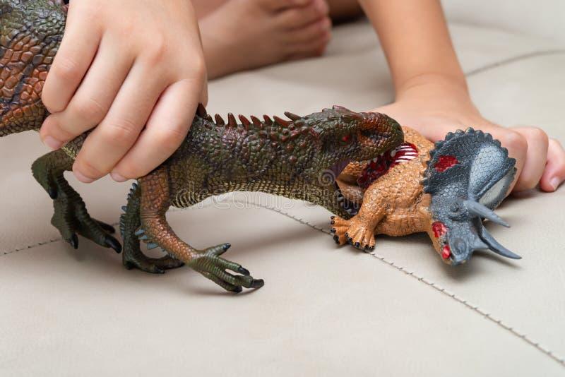 Unge som spelar med leksaker av den blodiga kroppen för Carcharodontosaurus och för triceratops på soffan royaltyfria bilder