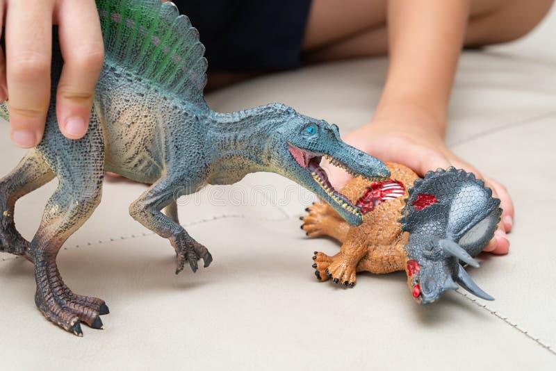 Unge som spelar med leksaker av den blodiga kroppen för spinosaurus och för triceratops på soffan arkivfoton