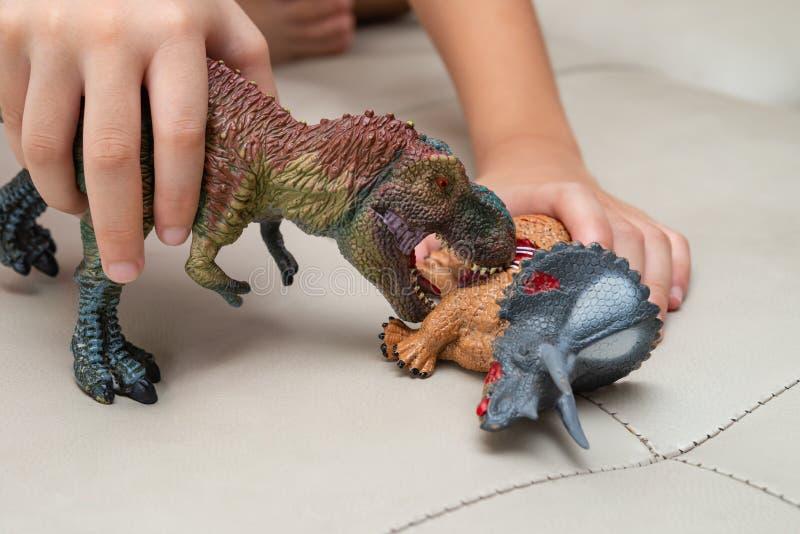 Unge som spelar med leksaker av den blodiga kroppen för tyrannosarie och för triceratops på soffan royaltyfri bild
