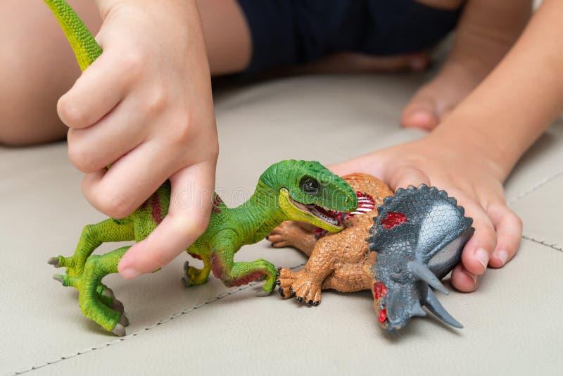 Unge som spelar med leksaker av den blodiga kroppen för velociraptor och för triceratops på soffan arkivbild