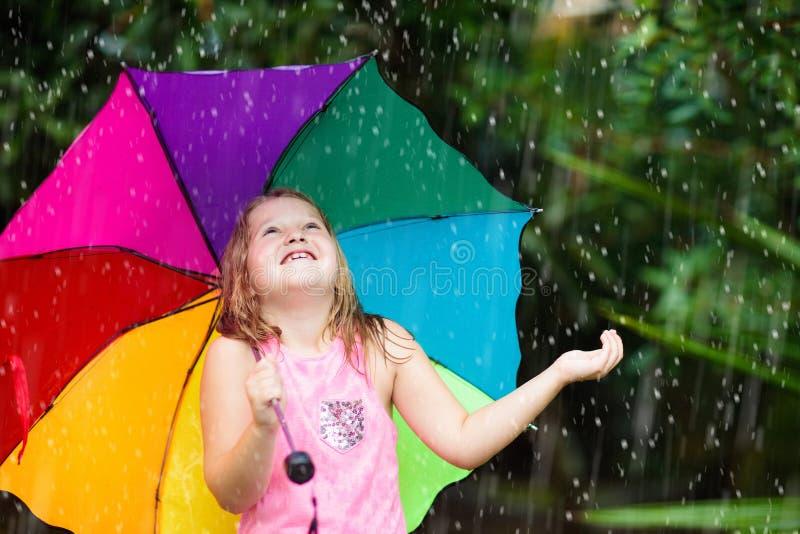 Unge som spelar ut i regnet Barn med paraply- och regnkängor att spela utomhus i hällregn Liten flicka som hoppar i lerigt royaltyfria bilder