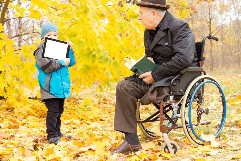 Unge som visar en handikappade personerman enPC royaltyfria bilder