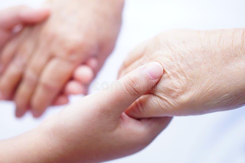 Ungebarn som rymmer höga för hand den asiatiska eller äldre patienten för den gamla damen med förälskelse, att bry sig, uppmuntra fotografering för bildbyråer