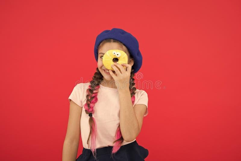 Ungefan av bakade donuts L?cker s?t munk Flicka i bakgrund f?r munk f?r baskerhatth?ll r?d ?ter den sk?mtsamma flickan f?r ungen  arkivbild