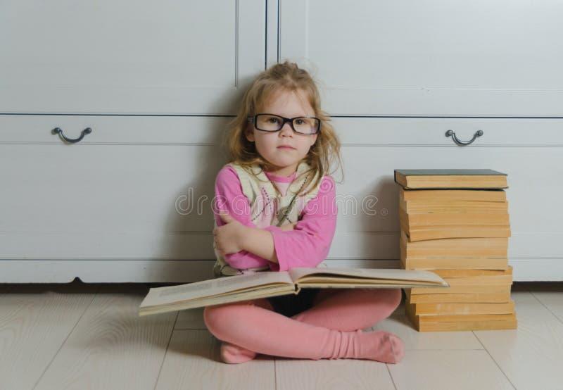 Ungeflicka med exponeringsglas och en bunt av böcker som sitter på golvet arkivbild