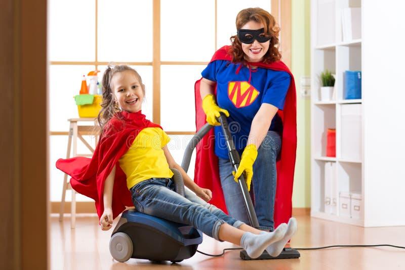 Ungeflicka och hennes moder weared Superherodräkter Det gulliga den hjälpredabarnet och kvinnan gör lokalvårdrum och har en gycke arkivbild