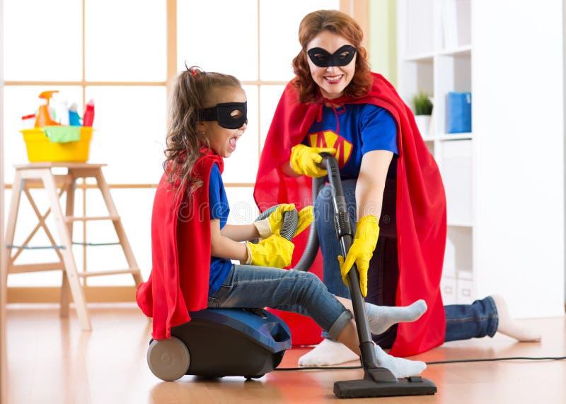 Ungeflicka och moder weared Superherodräkter Det gulliga den hjälpredabarnet och kvinnan gör lokalvårdrum och har en gyckel royaltyfri bild