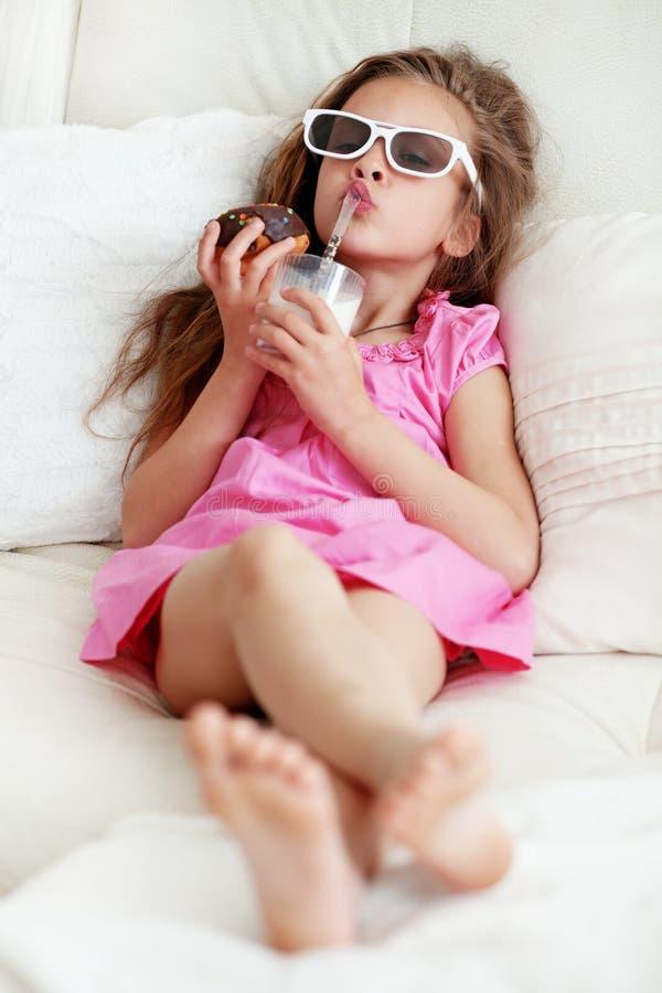 Ungeflicka som äter på en soffa royaltyfri foto
