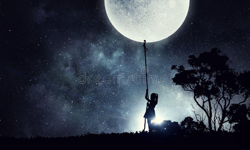 Ungeflicka som fångar månen fotografering för bildbyråer