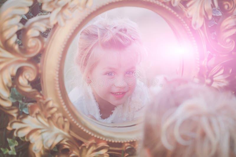 Ungeflickan reflekterar i spegel på solig dag arkivfoton