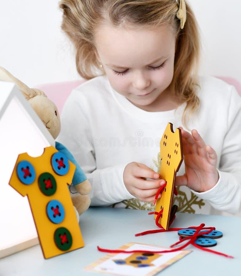 Ungeflickan spelar den bildande leken intresserat med den träfärgrika leksakt-skjortan med knappar och snör åt arkivfoto