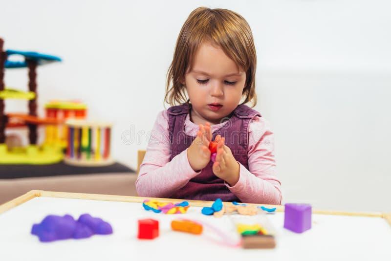 Ungeflickan spelar med plasticine, medan sitta på tabellen i barnkammarerum arkivbilder