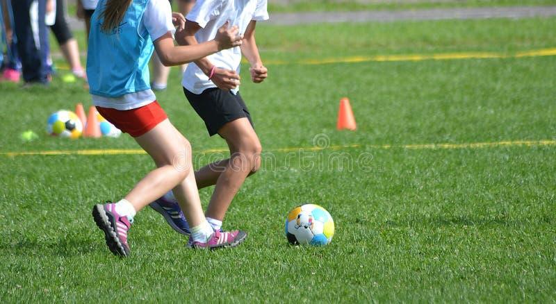 Ungeflickor spelar fotboll arkivbild