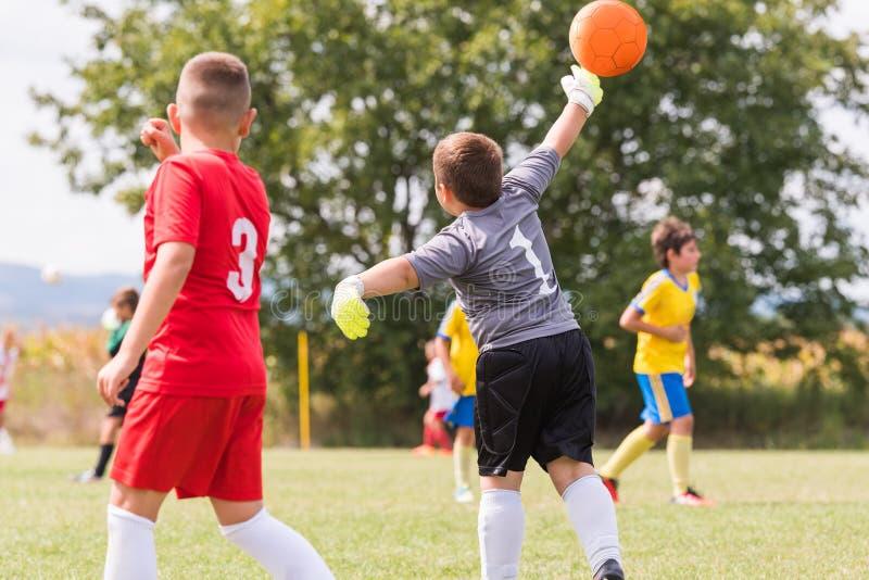 Ungefotbollfotboll - barnspelare matchar på fotbollfält arkivbild