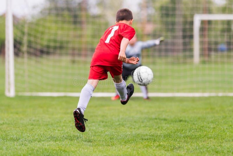 Ungefotbollfotboll - barnspelare matchar på fotbollfält royaltyfri foto