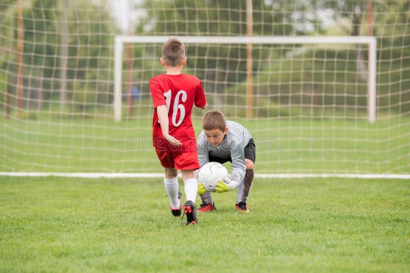 Ungefotbollfotboll - barnspelare matchar på fotbollfält arkivfoton