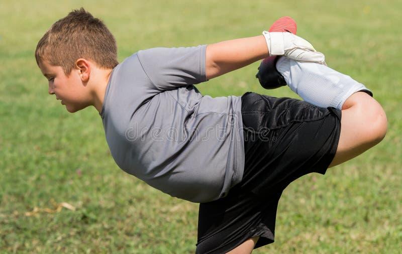 Ungefotbollfotboll - den lilla målvakten sträcker för så arkivfoton