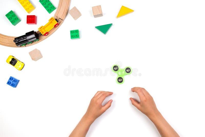 Ungehänder som spelar med rastlös människaspinnareleksaken Många färgrika leksaker på vit bakgrund arkivfoto