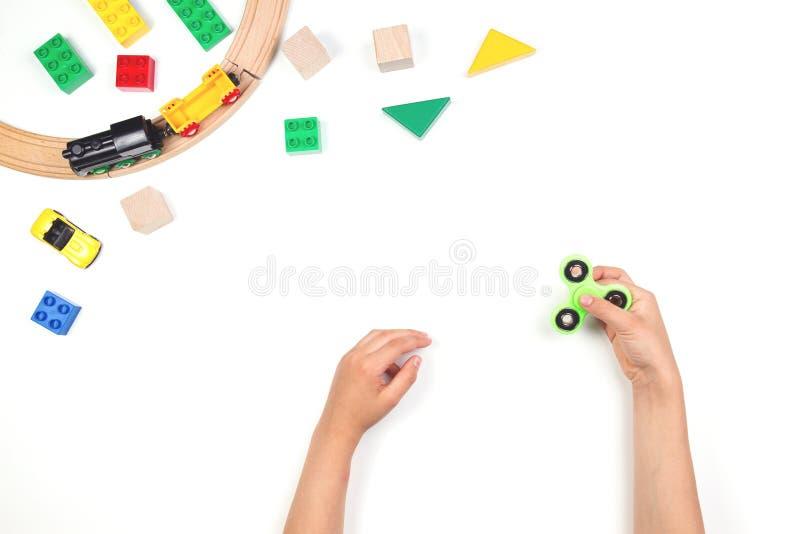 Ungehänder som spelar med rastlös människaspinnareleksaken Många färgrika leksaker på vit bakgrund royaltyfri fotografi