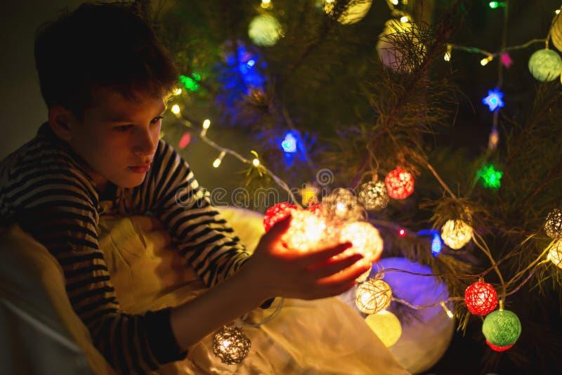 Ungeh?nder rymmer en bollgirland f?r jul eller nytt ?r hemma p? ljusbakgrund Ber?m f?r nytt ?r och jul arkivfoton