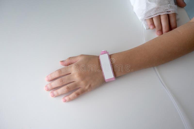 Ungehand som bär den rosa plast-namnetiketten på vit royaltyfria bilder