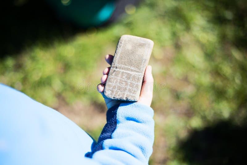 Ungehand som rymmer en stenmobiltelefon royaltyfri foto