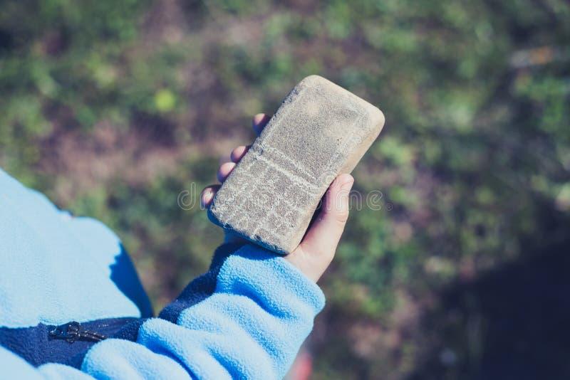 Ungehand som rymmer en stenmobiltelefon royaltyfria foton