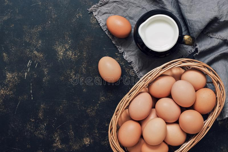 Ungekochte braune Eier in einem Korb und Milch in einem Krug auf einem dunklen rustikalen Hintergrund Draufsicht, Kopienraum lizenzfreie stockbilder