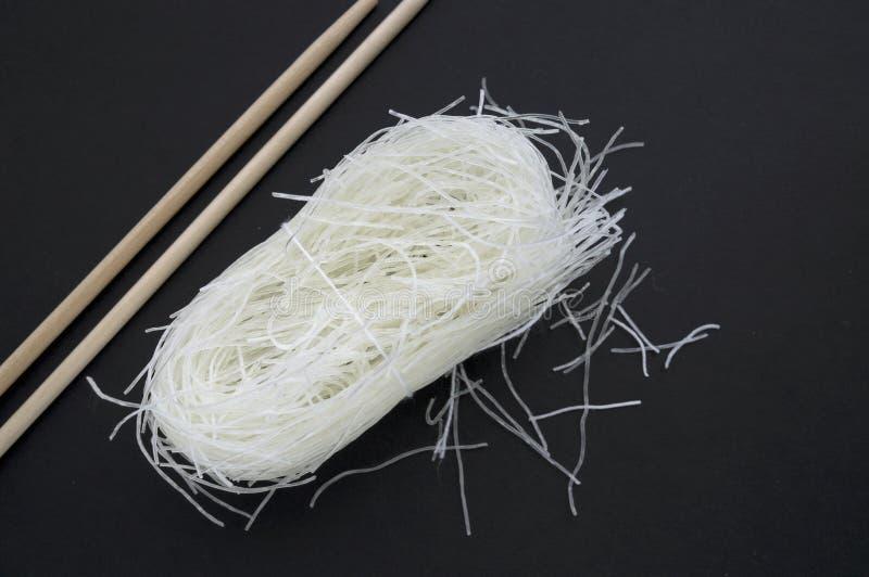 Ungekochte chinesische Zellophannudeln oder Glasnudeln auf schwarzer Oberfläche stockfotografie