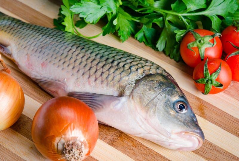 Ungekochte Fische auf Schneidebrett im Mahlzeitvorbereitungskonzept stockfotografie