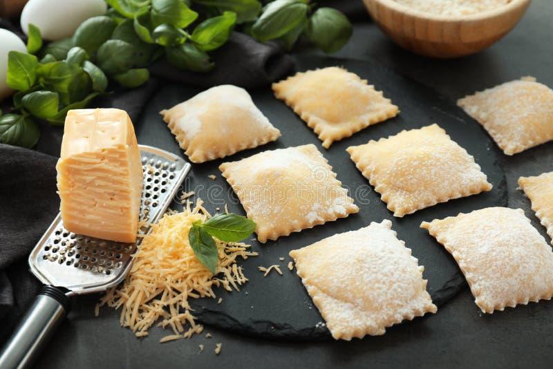 Ungekochte Ravioli mit geriebenem Käse auf dunkler Tabelle lizenzfreies stockfoto
