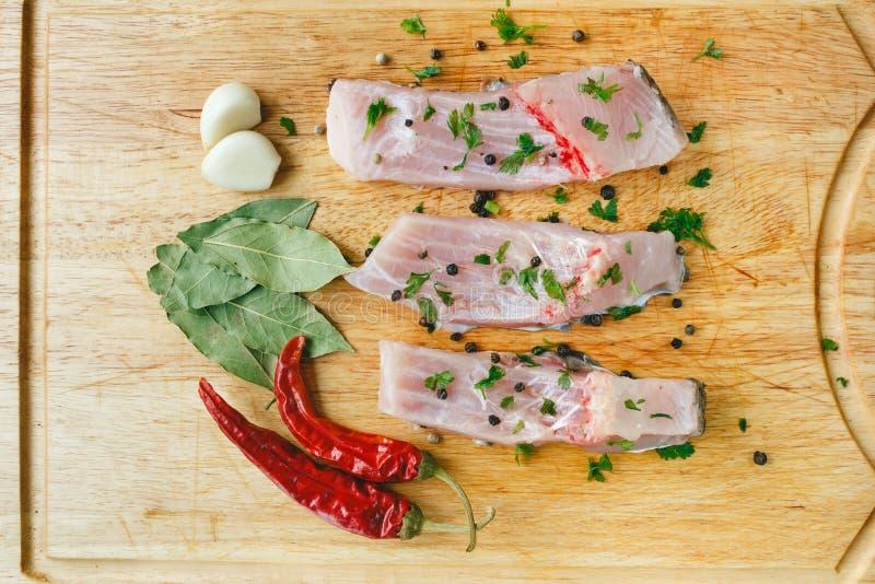 Ungekochte Silbermünzekarpfenfische mit Pfeffer des roten Paprikas, Lorbeerblatt, Gewürzen und Knoblauch auf hölzernem Brett, Dra stockbilder