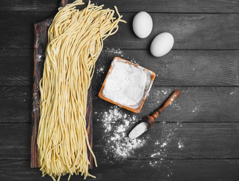 Ungekochte Spaghettinudeln an Bord stockbilder