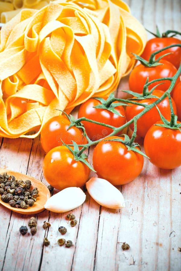 Ungekochte Teigwaren, frische Tomaten und Gewürze lizenzfreie stockfotografie