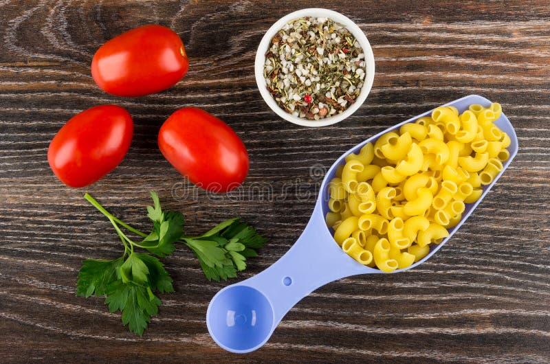 Ungekochte Teigwaren im Löffel, in den Tomaten, in der Petersilie und im Gewürz auf tabl stockbild