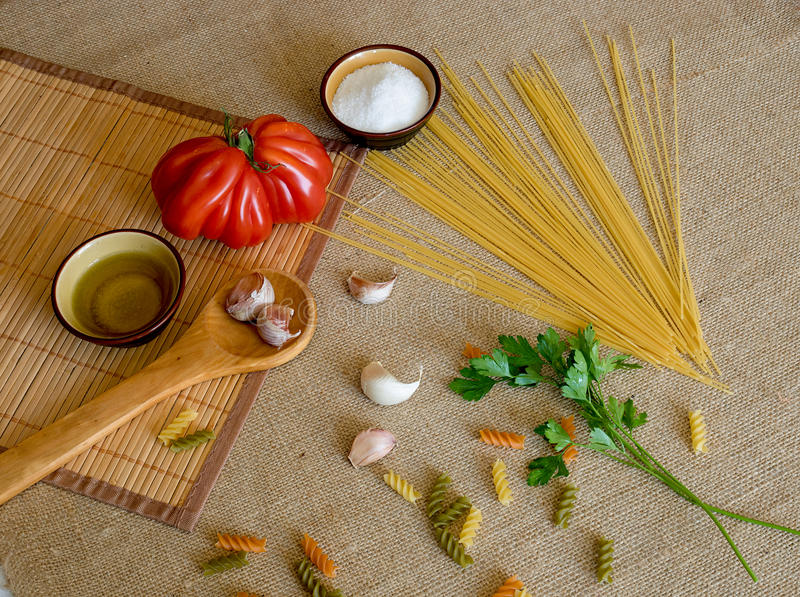 Ungekochte trockene Spaghettis auf rustikale Oberflächen mit Tomate, Knoblauch, stockfoto