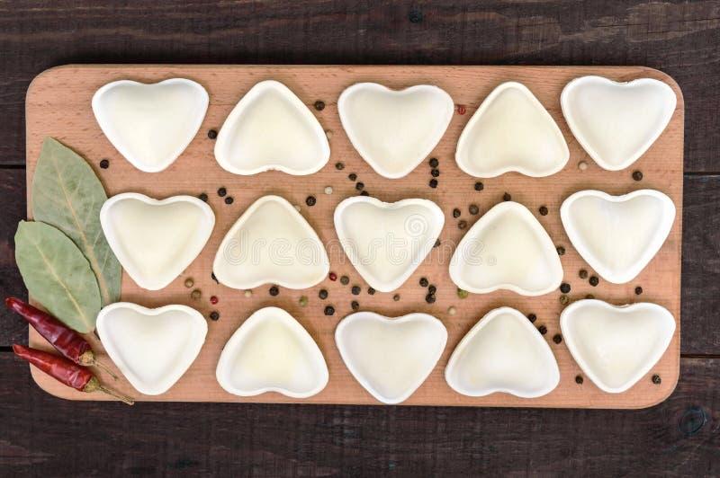 Ungekochter Teig in Form der Mehlklöße eines Herzens, Ravioli, pelmeni, auf einem Schneidebrett lizenzfreies stockfoto