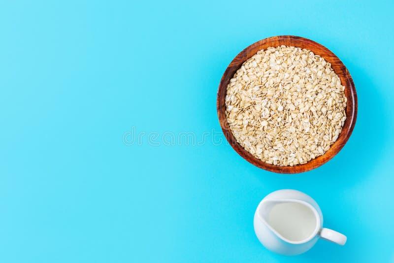 Ungekochtes Haferflocken in der Bambusschüsselpflanzenmilch im weißen keramischen Krug auf hellblauer Tischplatte Gesundes Fr?hst lizenzfreie stockfotos
