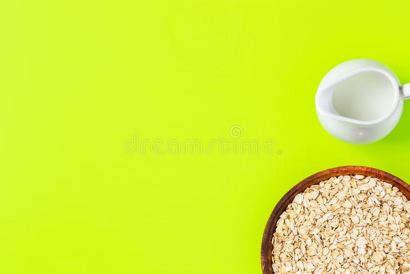Ungekochtes Haferflocken in der Bambusschüsselpflanzenmilch im weißen keramischen Krug auf hellgrünem Tischplattenhintergrund Ges stockfotos