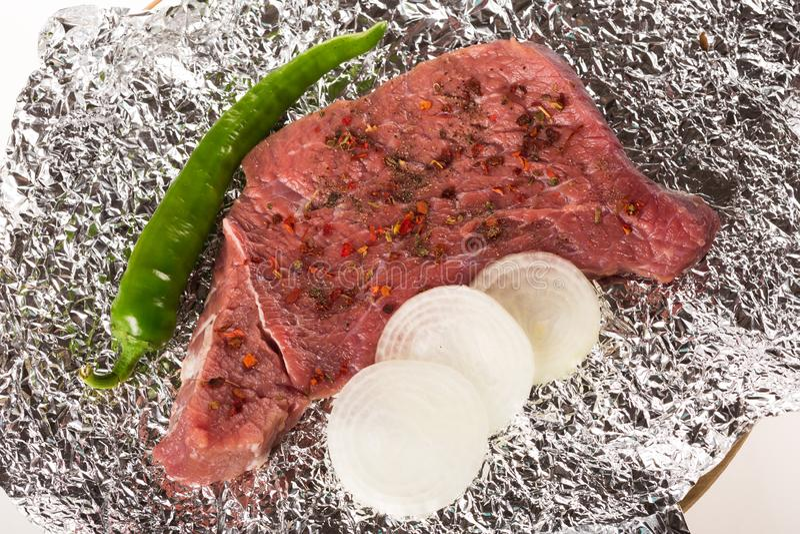 Ungekochtes Steak auf Folie mit Kräutern und spicies, Zwiebel, Pfeffer stockbild