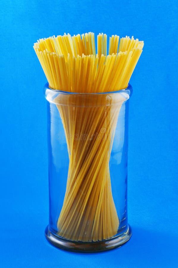 Ungekochtes Teigwarenspaghettimakkaroni auf blauem Hintergrund lizenzfreies stockbild