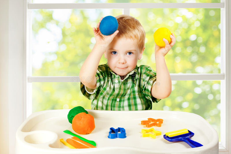 Ungelek som modellerar plastellina, barnet och färgrika Clay Dough, leksaker arkivbild