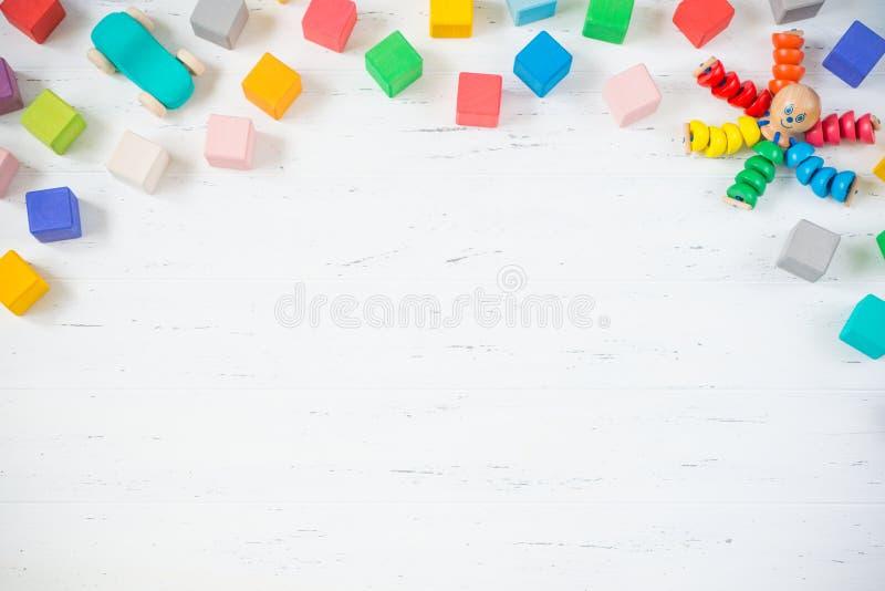 Ungeleksaker inramar träkvarter, bläckfisken, bil på vit träbakgrund Top beskådar Lekmanna- lägenhet royaltyfri bild