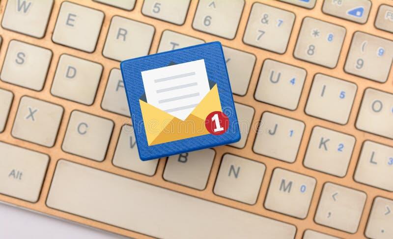 Ungelesene E-Mail-Ikone auf Würfeln mit Tastatur im Hintergrund lizenzfreies stockbild