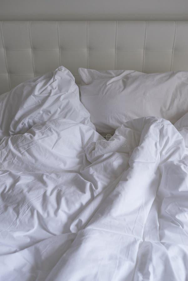 Ungemachtes Bett mit einfacher weißer Bettwäsche stockbild