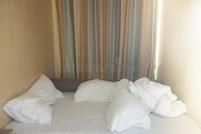 Ungemachtes Bett mit zerknitterten Bettlaken und Kissen stockbilder