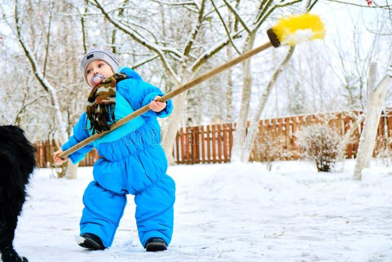 Ungen gör klar snön nära huset arkivbild