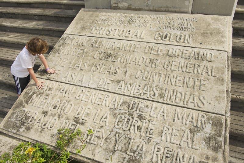 Ungen läser den minnes- plattan på ingången till Columbus Lighthouse i Santo Domingo, Dominikanska republiken royaltyfri foto